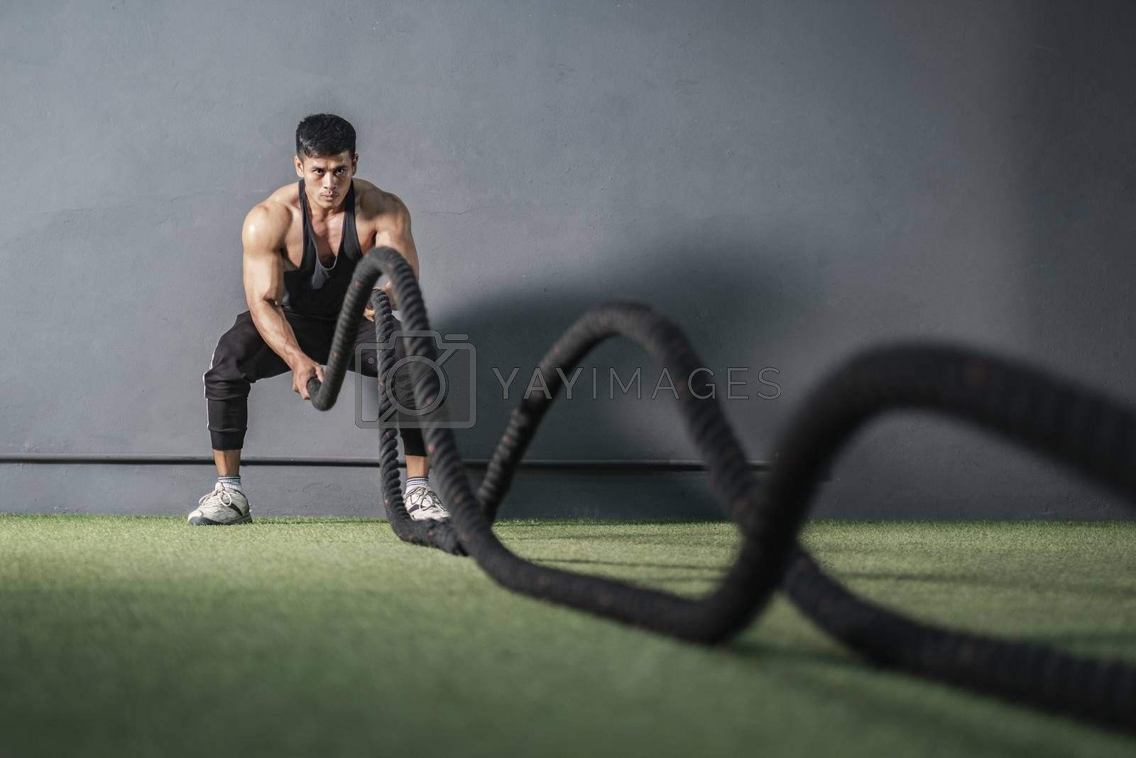 Strong muscle man workout with rope in training fitness gym