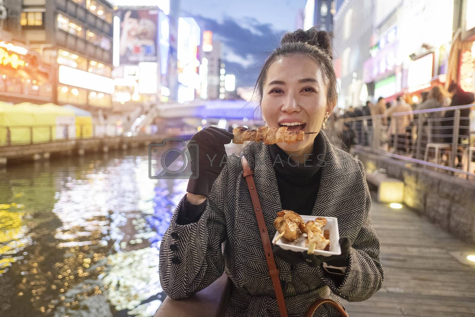 Young woman tourists enjoy eating street food in walking at street shopping center Dotonbori in Osaka, Japan.
