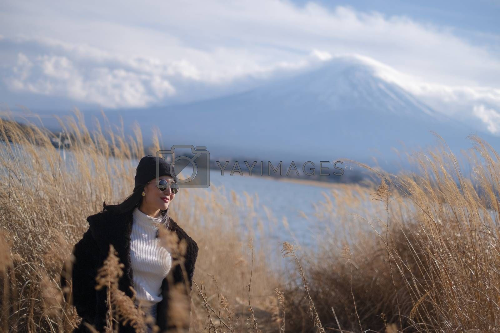 Beautiful smiling woman tourists are traveling and feel happy with Mt Fuji in the morning on the lake kawaguchiko, Japan