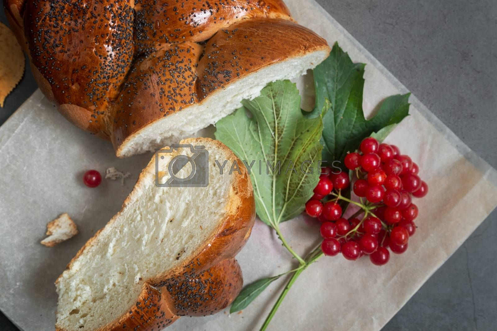On the table is a sliced loaf of white bread with a crisp crust sprinkled with poppy seeds. Next to the knife and viburnum berries. Front view, dark background, copy space