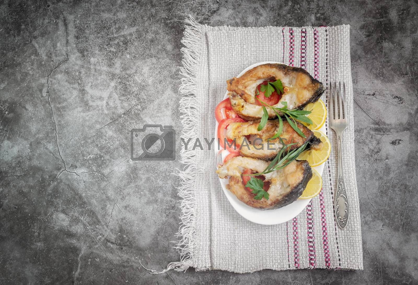 On the table on a plate pieces of fried carp with tomatoes and lemon. Top view, copy space