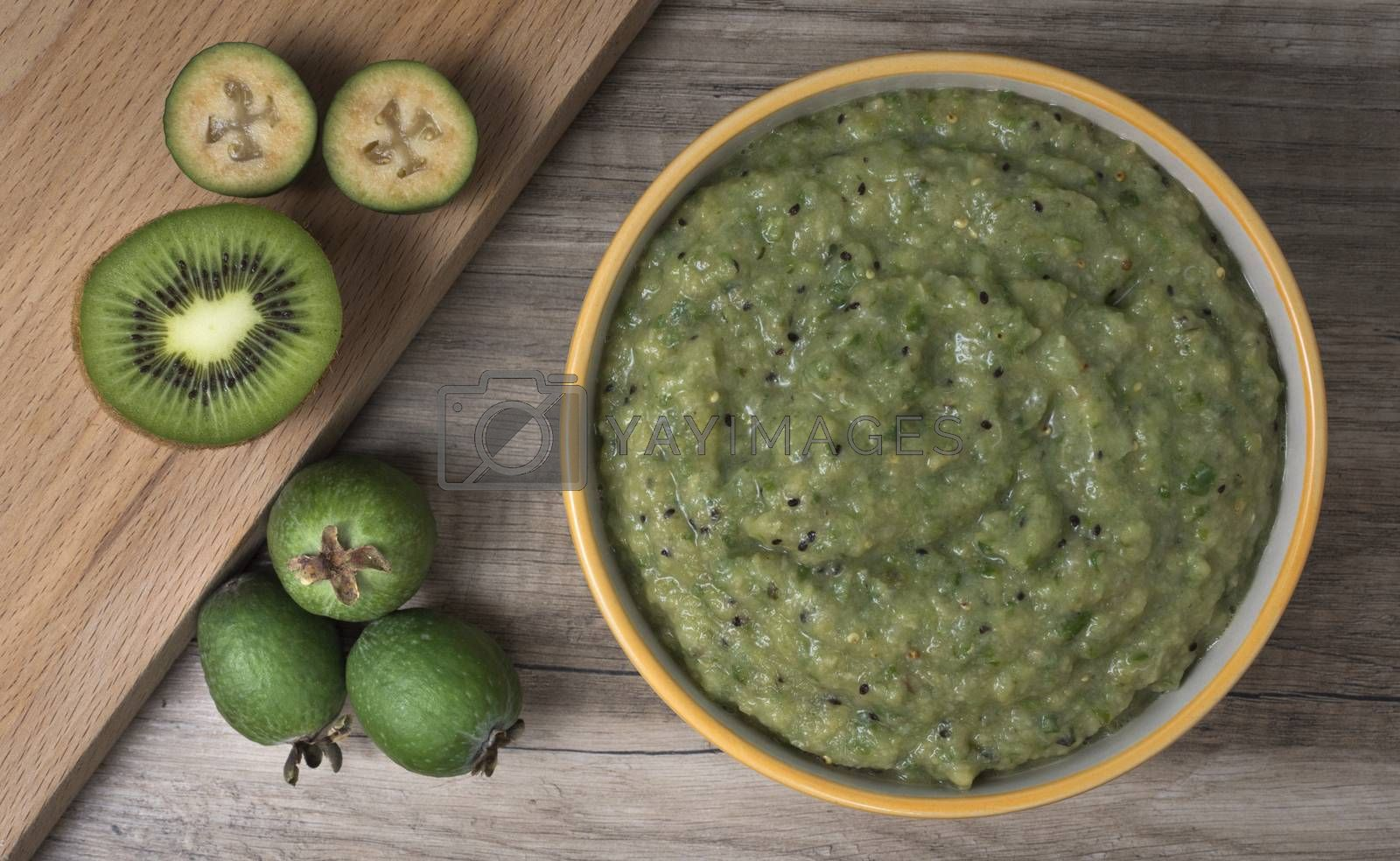 Royalty free image of Ceramic bowl with mashed feijoa with kiwi and sugar. by phortcach