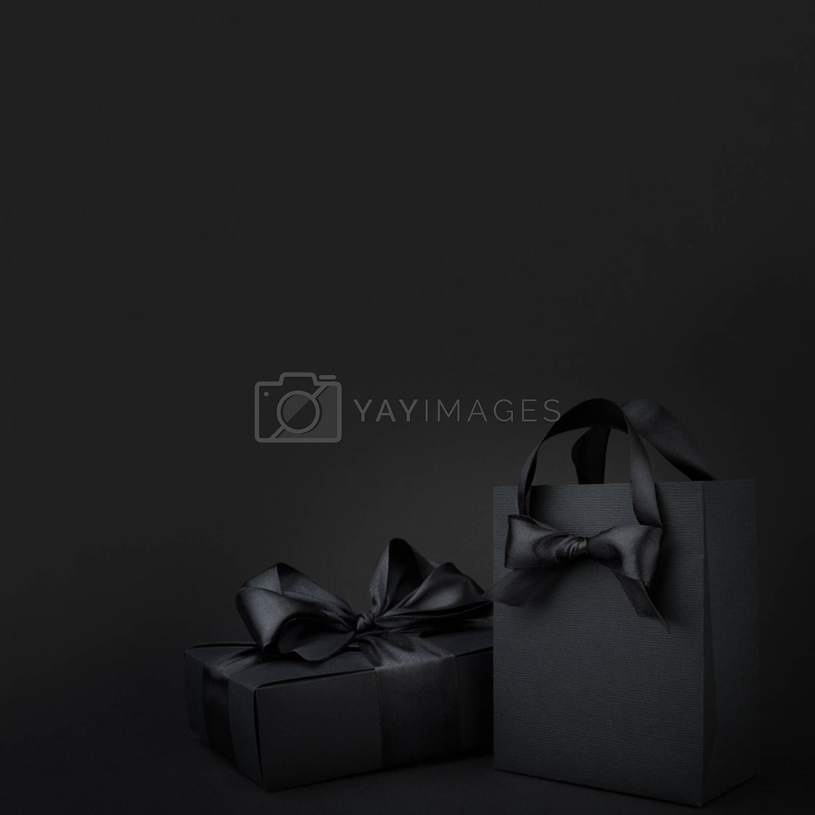 Concept sales, shopping, black friday. Paper shopping or gift bag box with silk ribbon bow on black background with copy space
