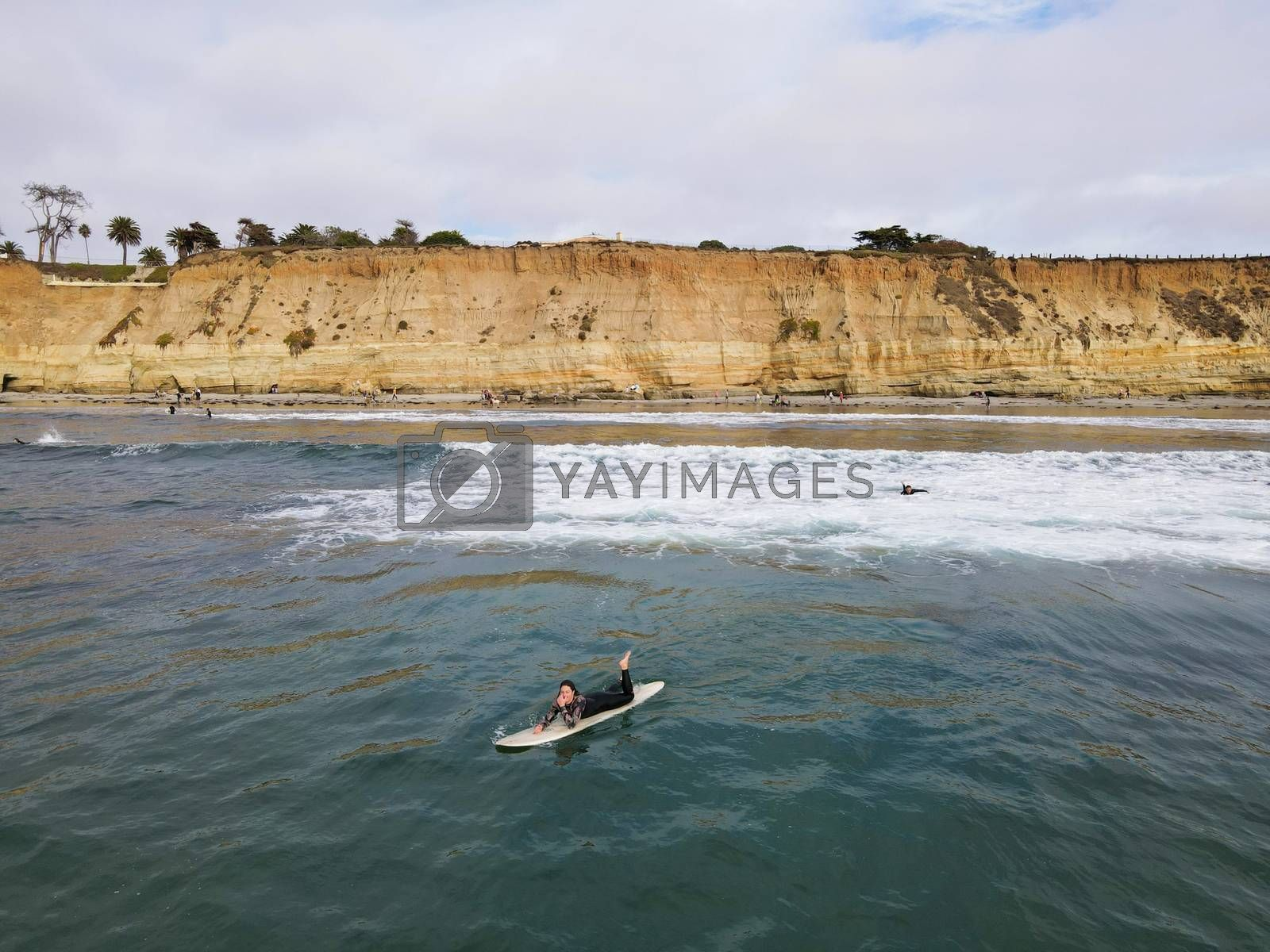 Surfers with wet suit paddling and enjoying the big waves. San Diego, California, USA. November 20th, 2020