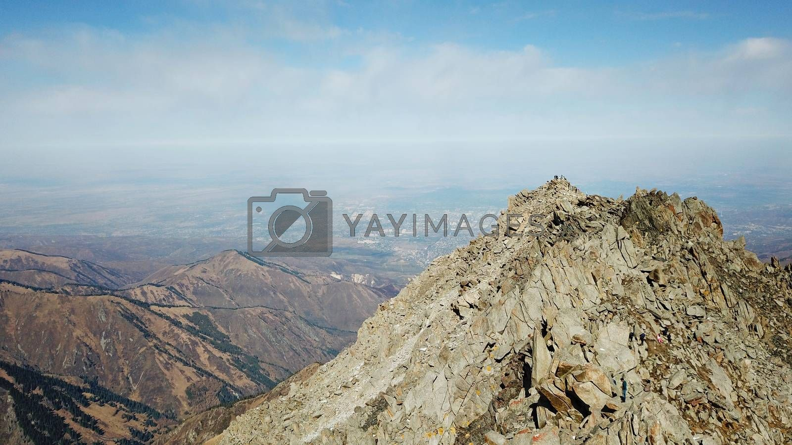 Top view of a group of tourists on top of a snowy peak. Huge rocks covered with snow. Climbers take photos from the top, pose. Flying above the mountains. Blue sky and steep slopes. Kazakhstan.