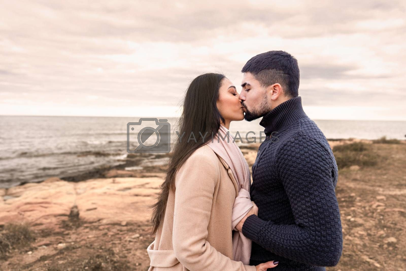 Mixed race couple romance scene on sea rocks and cloudy sky at sunset or dawn - Handsome bearded guy kisses his beautiful black Hispanic long hair woman holding her by the scarf with autumn colors