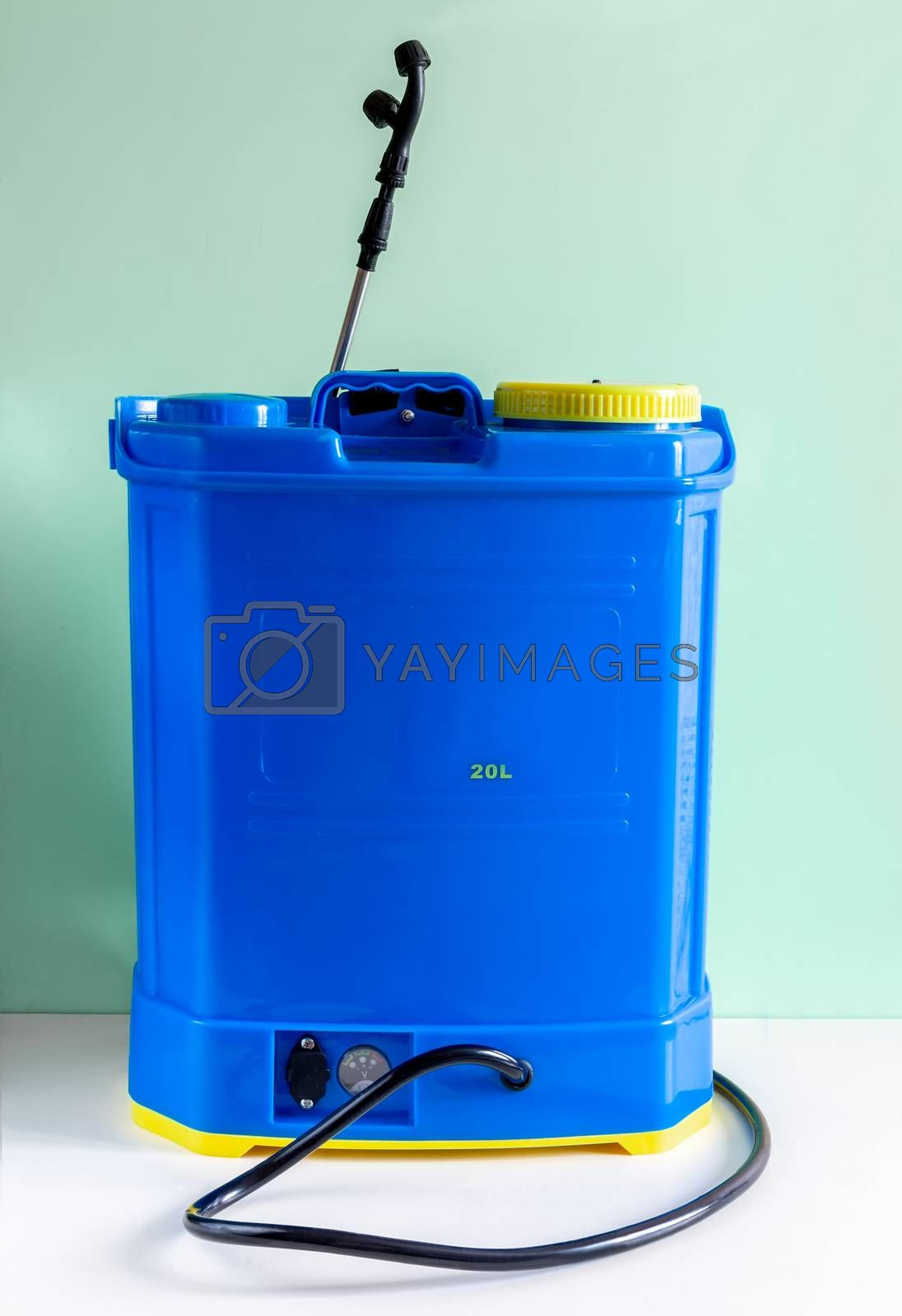 Backpack battery sprayer for protecting trees and plants from diseases and pests. The pressure is increased using a battery-powered pump. Facade. Copy space