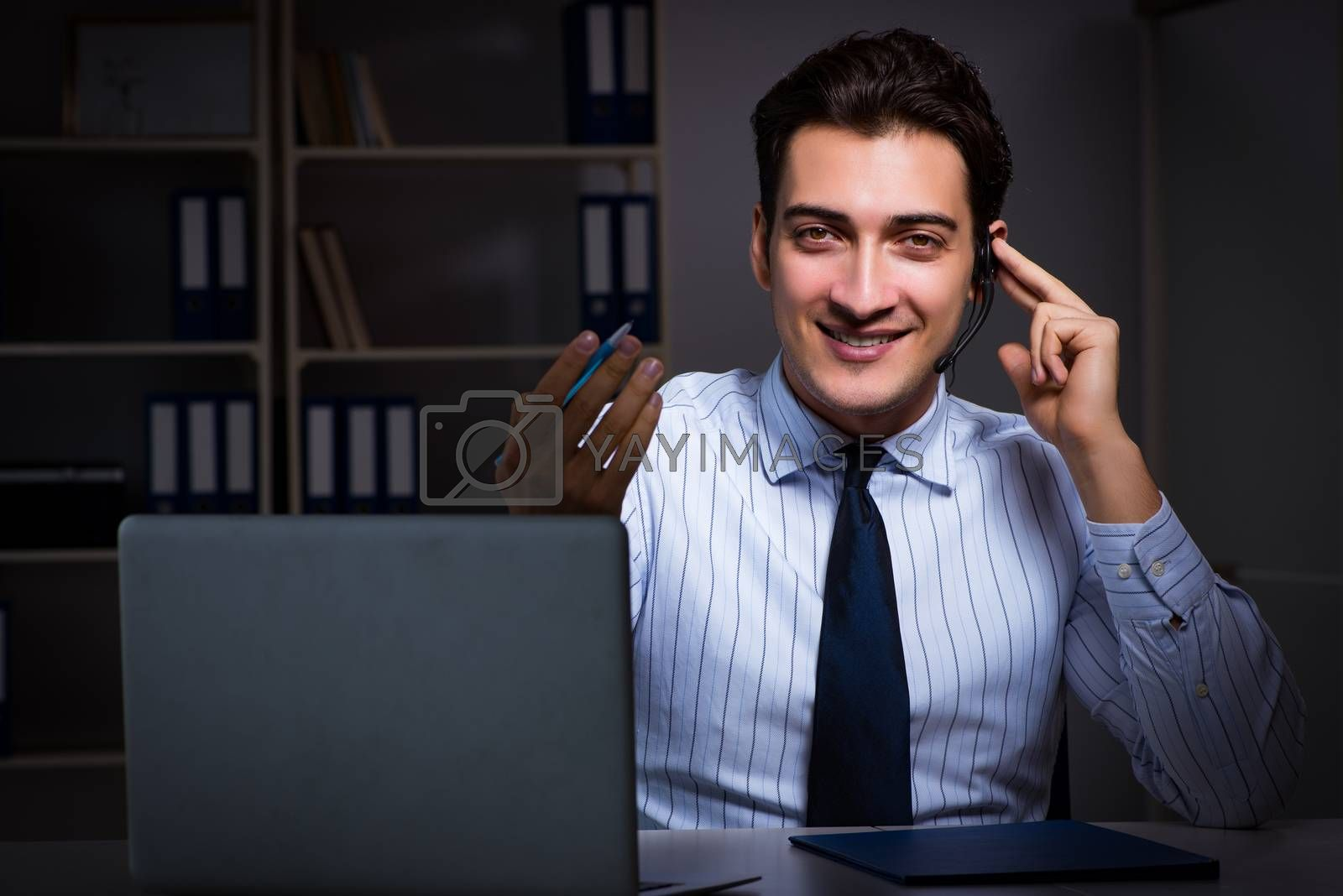 Call center operator talking to customer during night shift