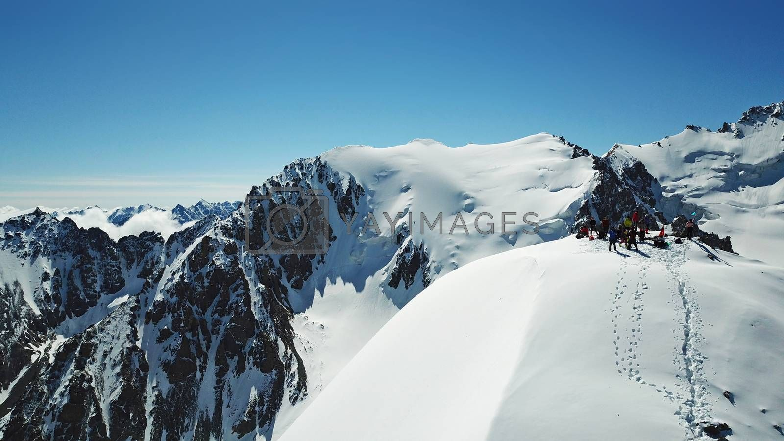 A group of climbers climb to the top of the peak. Dangerous, steep slope. Avalanche-prone area. Mountains covered with snow. Steep cliffs and large rocks. Above the mountains, top view from a drone.