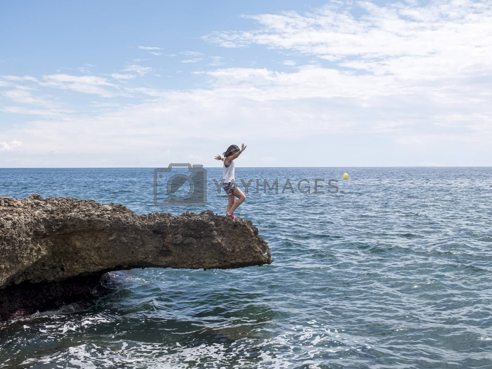 Side view of a woman standing on sea rocks