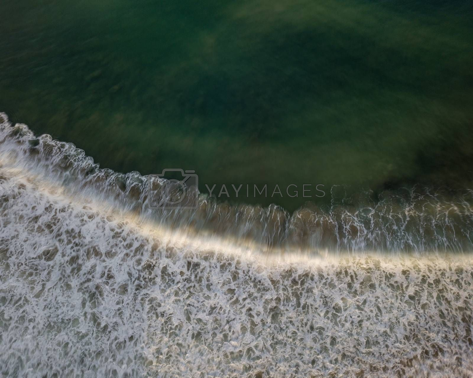 Top down aerial view of sea water and wave. Green ocean water and foam background with motion blur.