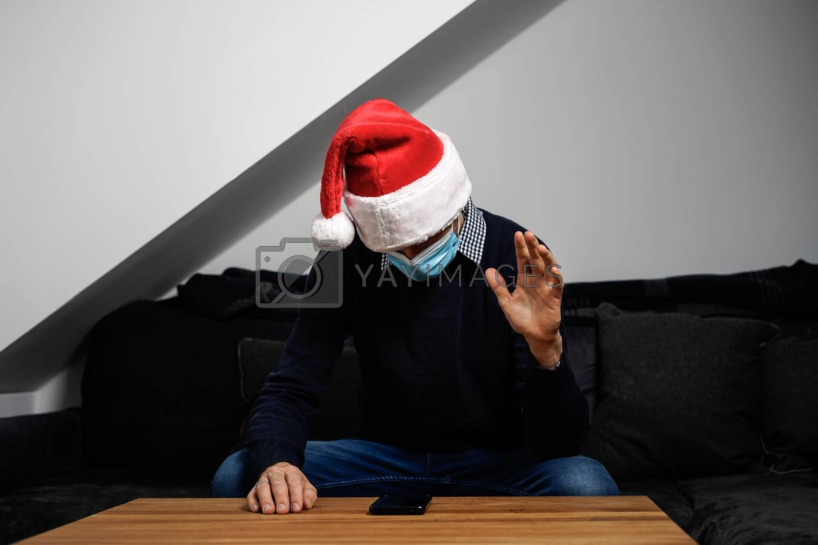 young man with santa hat has an online christmas party during the coronavirus pandemic.