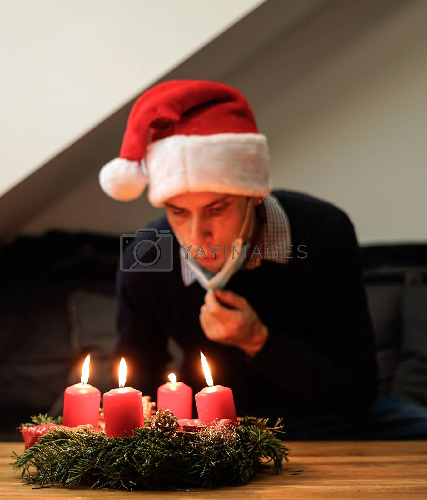 young man blowing out candles from christmas wreath. celebrate christmas alone due to the corona pandemic.