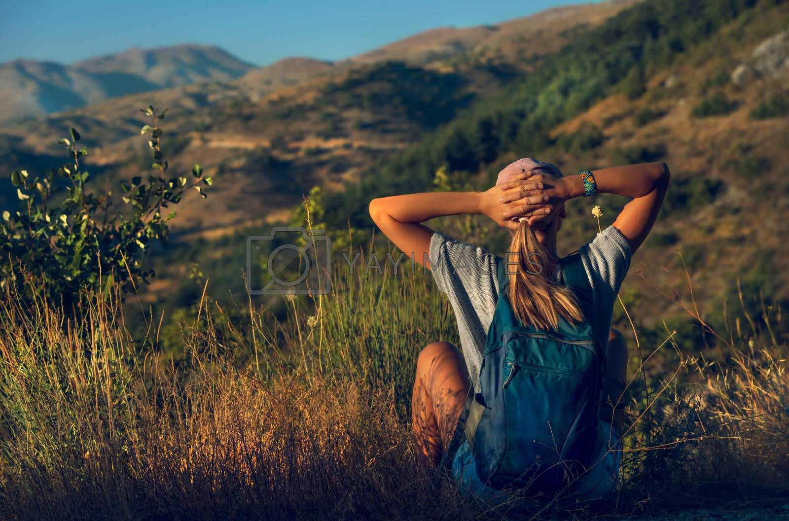 Back Side of a Young Girl Sitting on the Mountain Top and Enjoying Amazing Mountainous View. Active Summer Vacation.