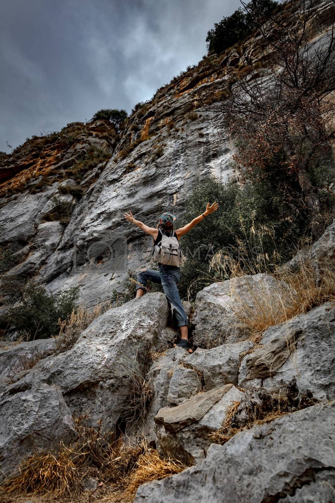 Active Sportive Woman Climbing the Mountains. Carefully Backpacker Сlimbs Up to Tannourine Picks. Extreme Vacation in Lebanon.
