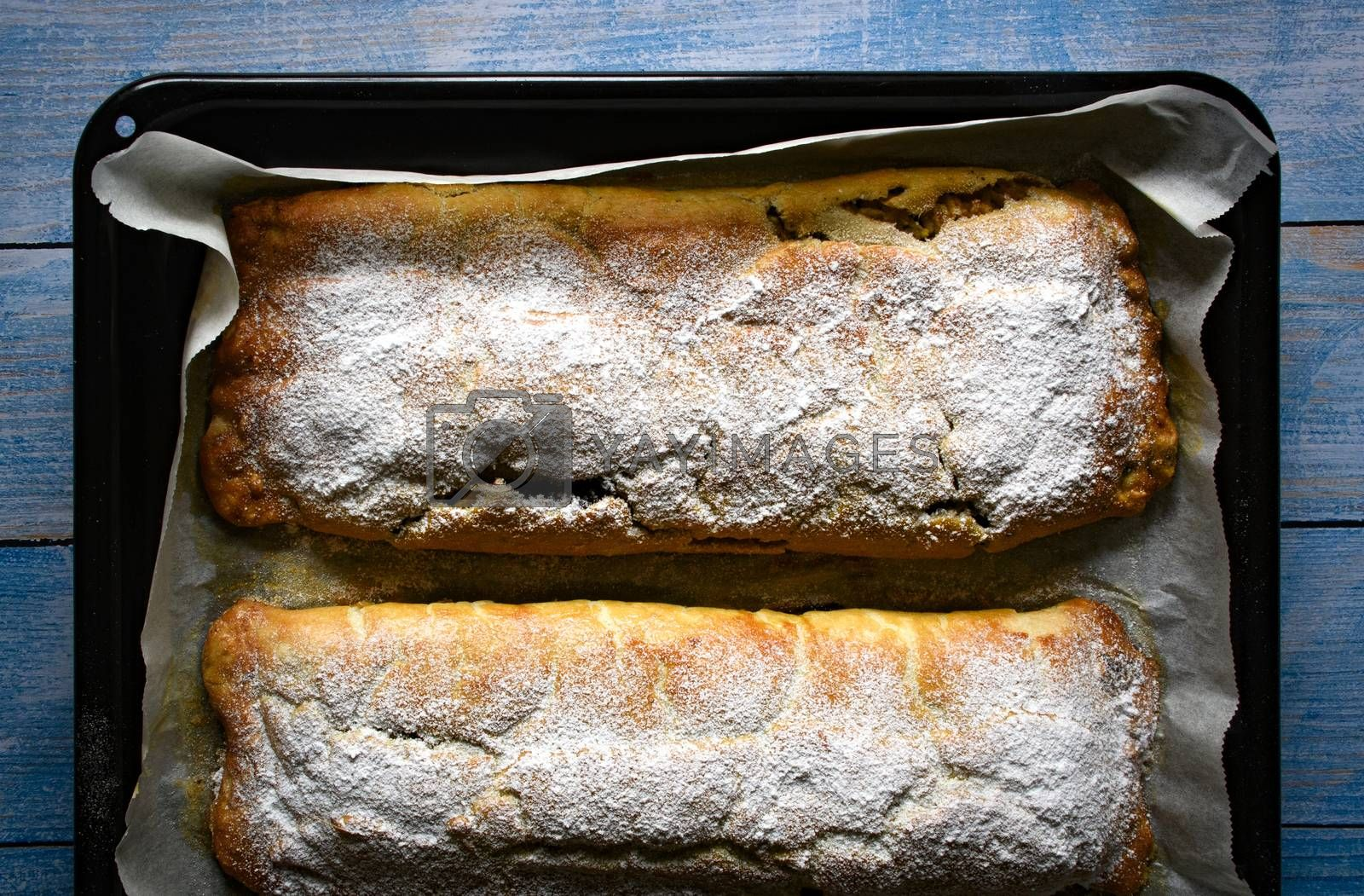 food background freshly baked strudel on a black baking tray