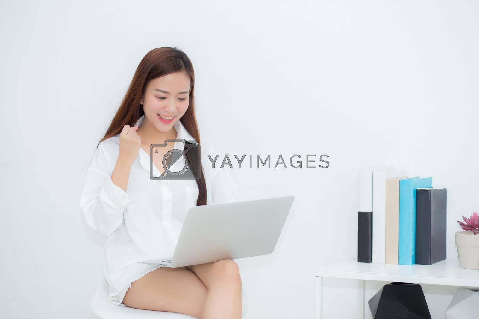 Beautiful of portrait happy young asian woman using laptop work with success on chair in the home, girl and notebook shopping online with glad, communication concept.