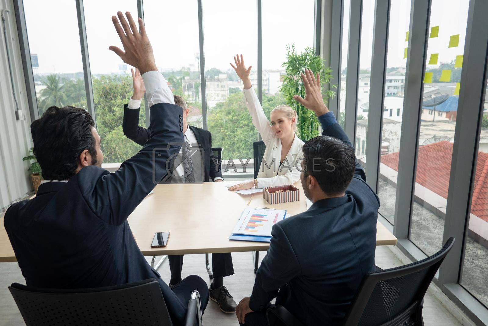 Royalty free image of young business people raise their hands up for vote in the meeting. Stack of hands. Unity, teamwork concept by chuanchai