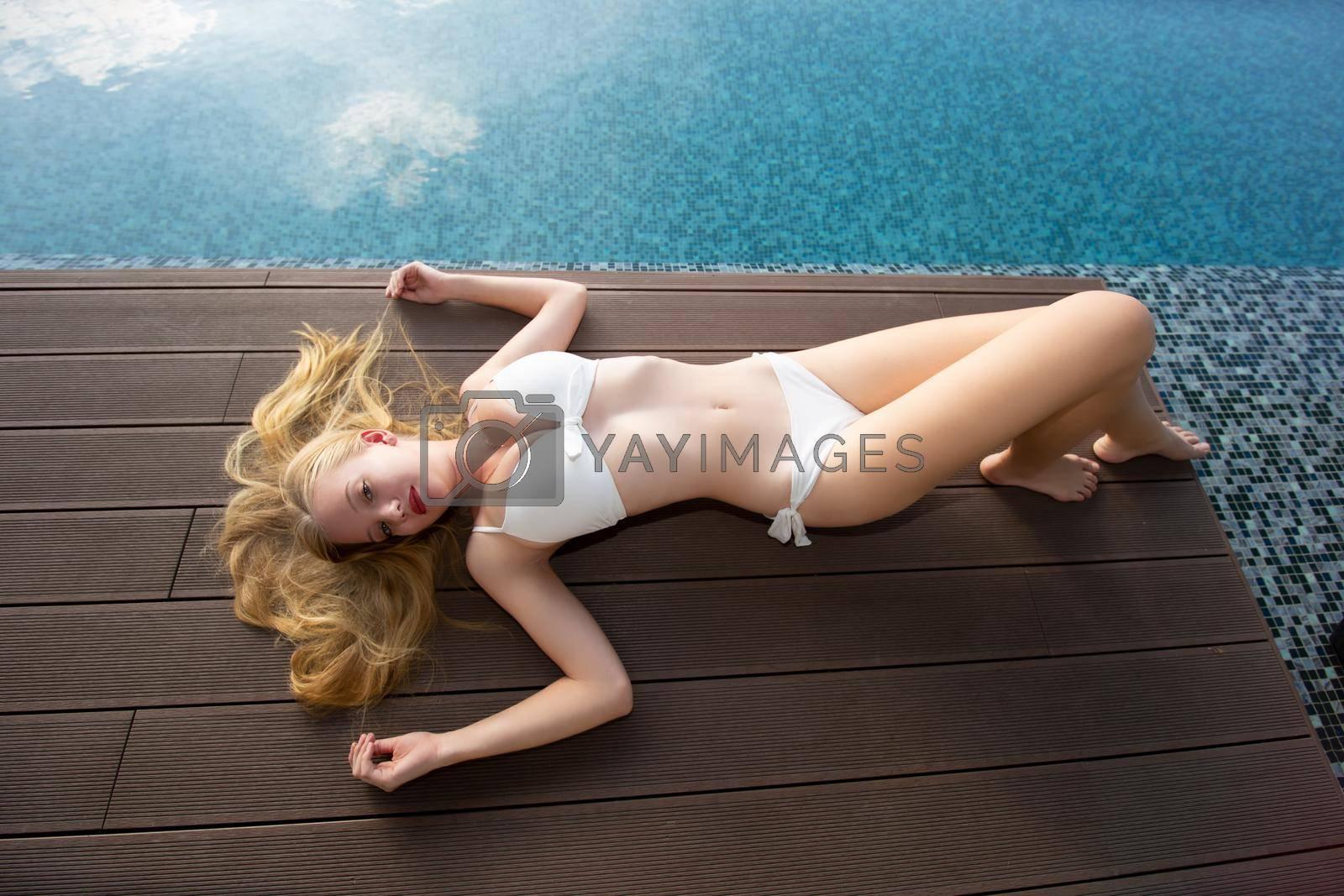 Young woman enjoying a sun, Slim young girl model in white bikini  by the pool.