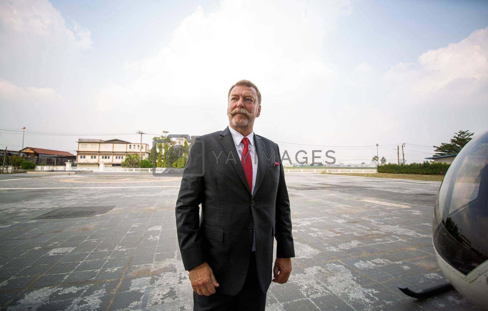 confident business people standing against his private helicopter at landing airport. Professional career success concept