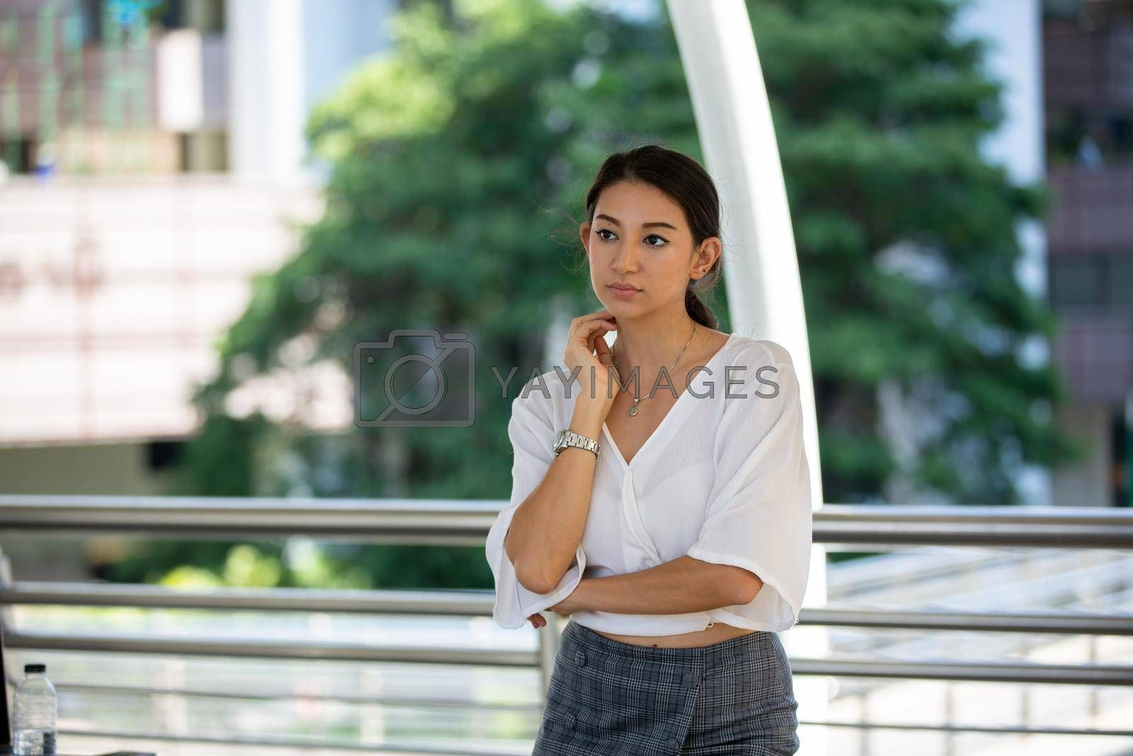 Portrait of young beautiful business woman at outside. Crossed arms