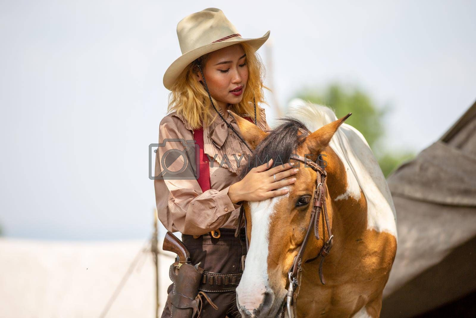 Cowgirl standing by horse at outdoor.