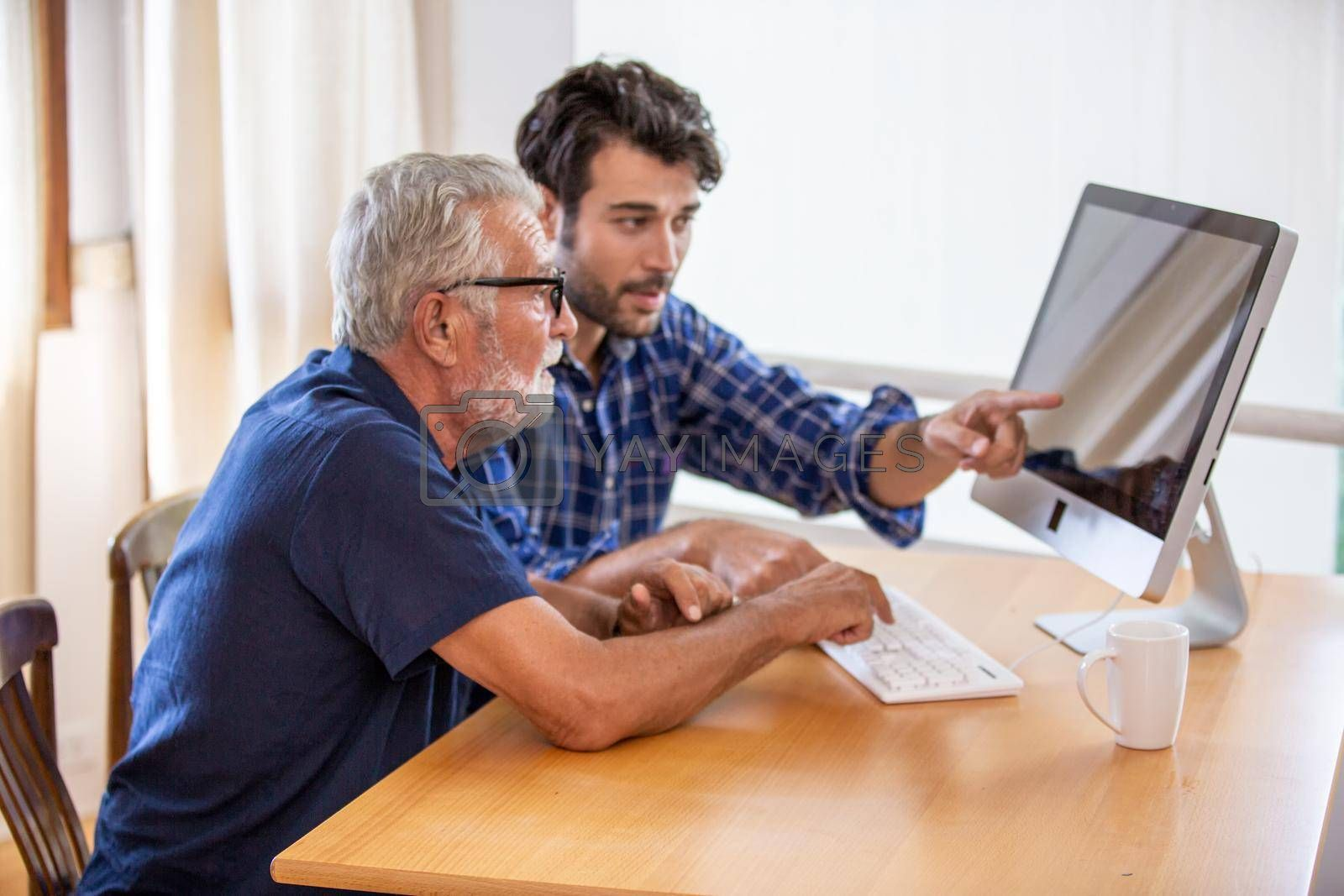 man teaching elderly man to using computer