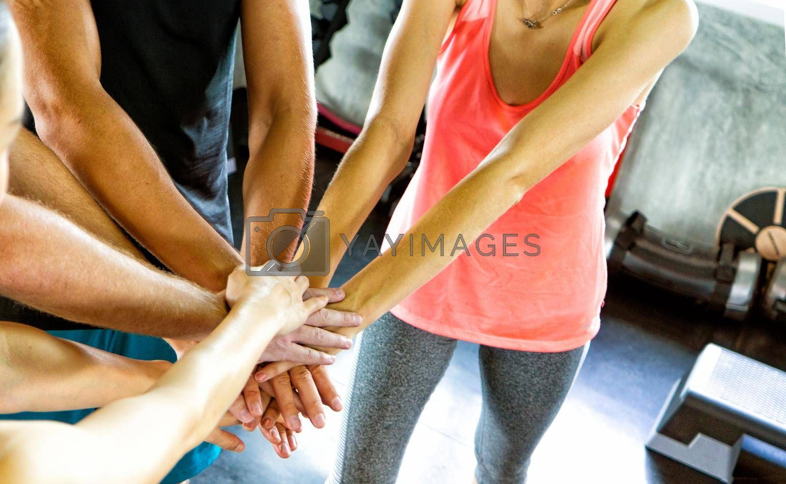 Athletic young people in sportswear doing fitness stretching exercises at fitness gym. Sport and recreation concept.