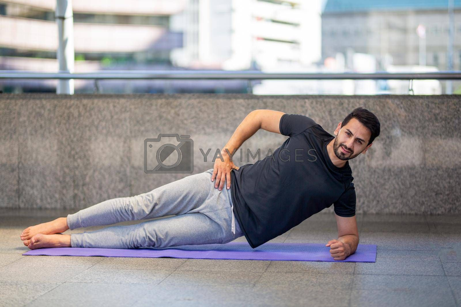Young attractive smiling man practicing yoga pose, working out, wearing sportswear pants, full length, outdoor.