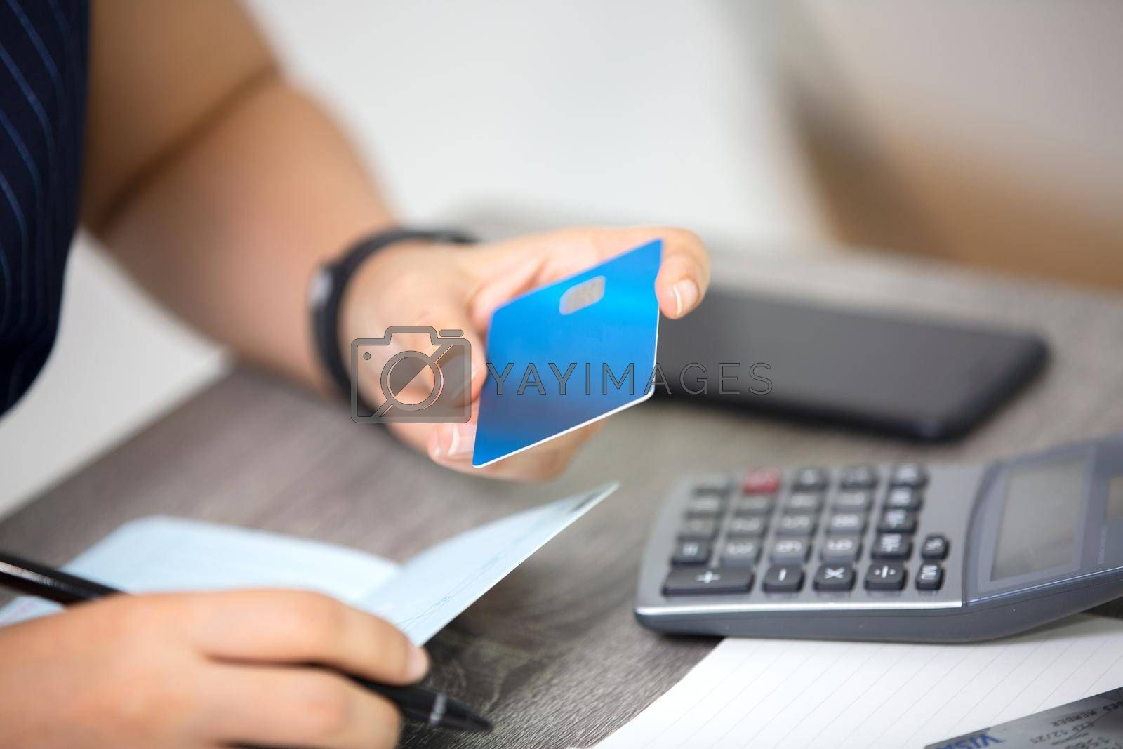midsection of woman with credit card book bank and calculator paying bills online indoor