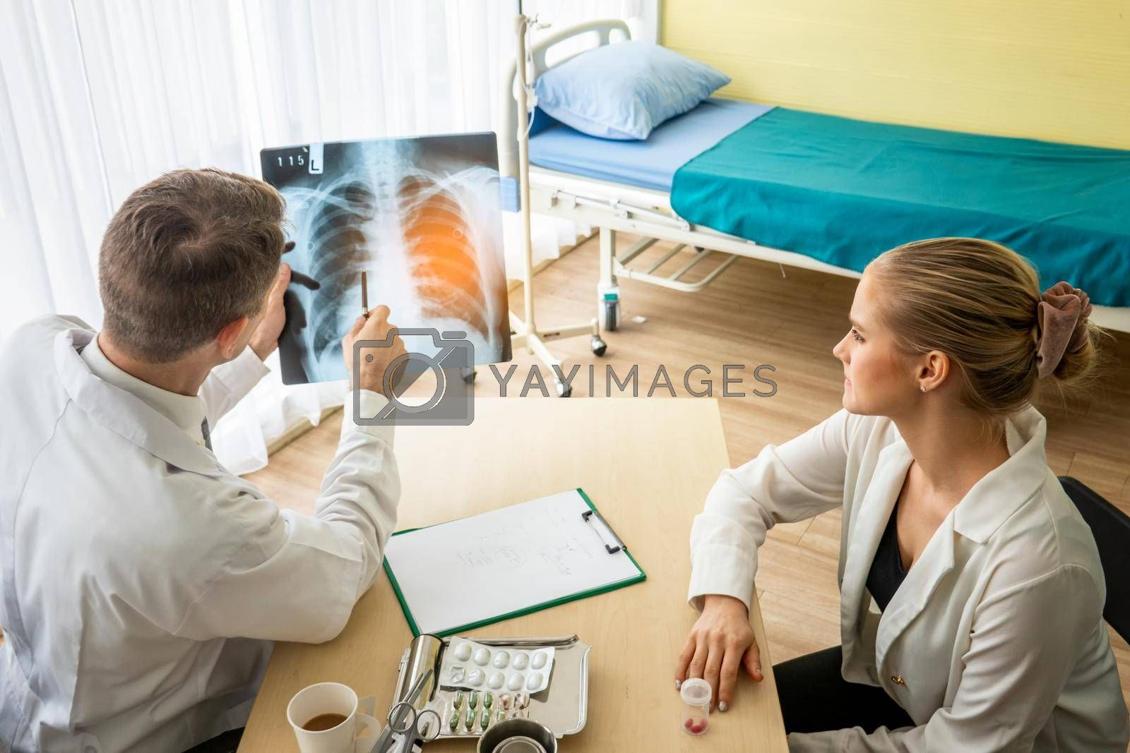 Doctor explaining lungs x-ray to women patient in clinic or Doctor in the office examining an x-ray and discussing with a patient
