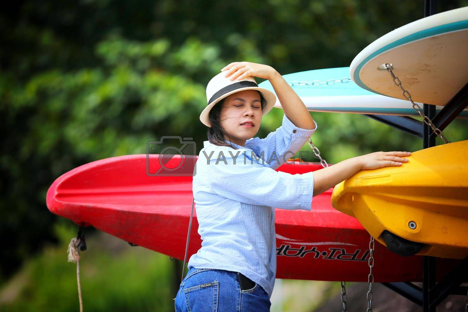portrait of young Asian woman showing long braided standing by surfboard.