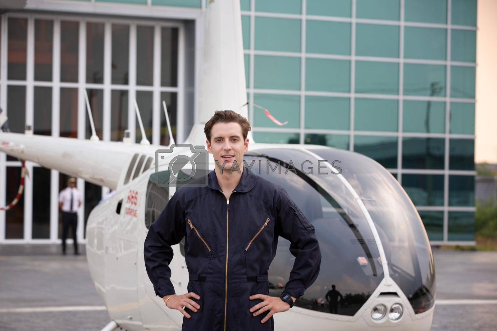 Commercial man pilot in technician suit standing in front of helicopter after check and maintenance engine by chuanchai