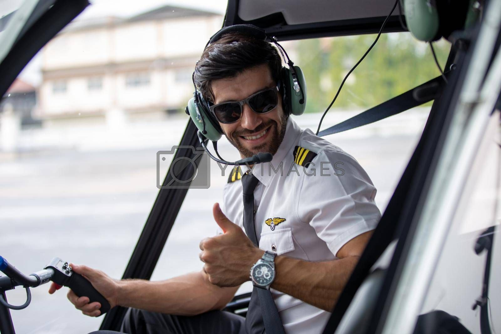 Shot of a mature Helicopter pilot using a headset while traveling in a helicopter, Business people traveling by helicopter