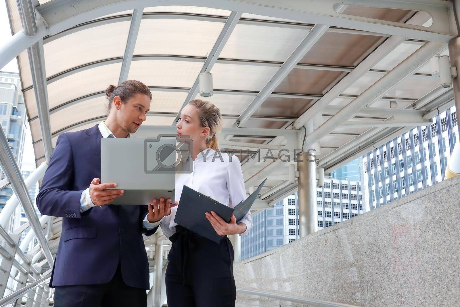 Businessman and businesswoman discussing work while walking outside office