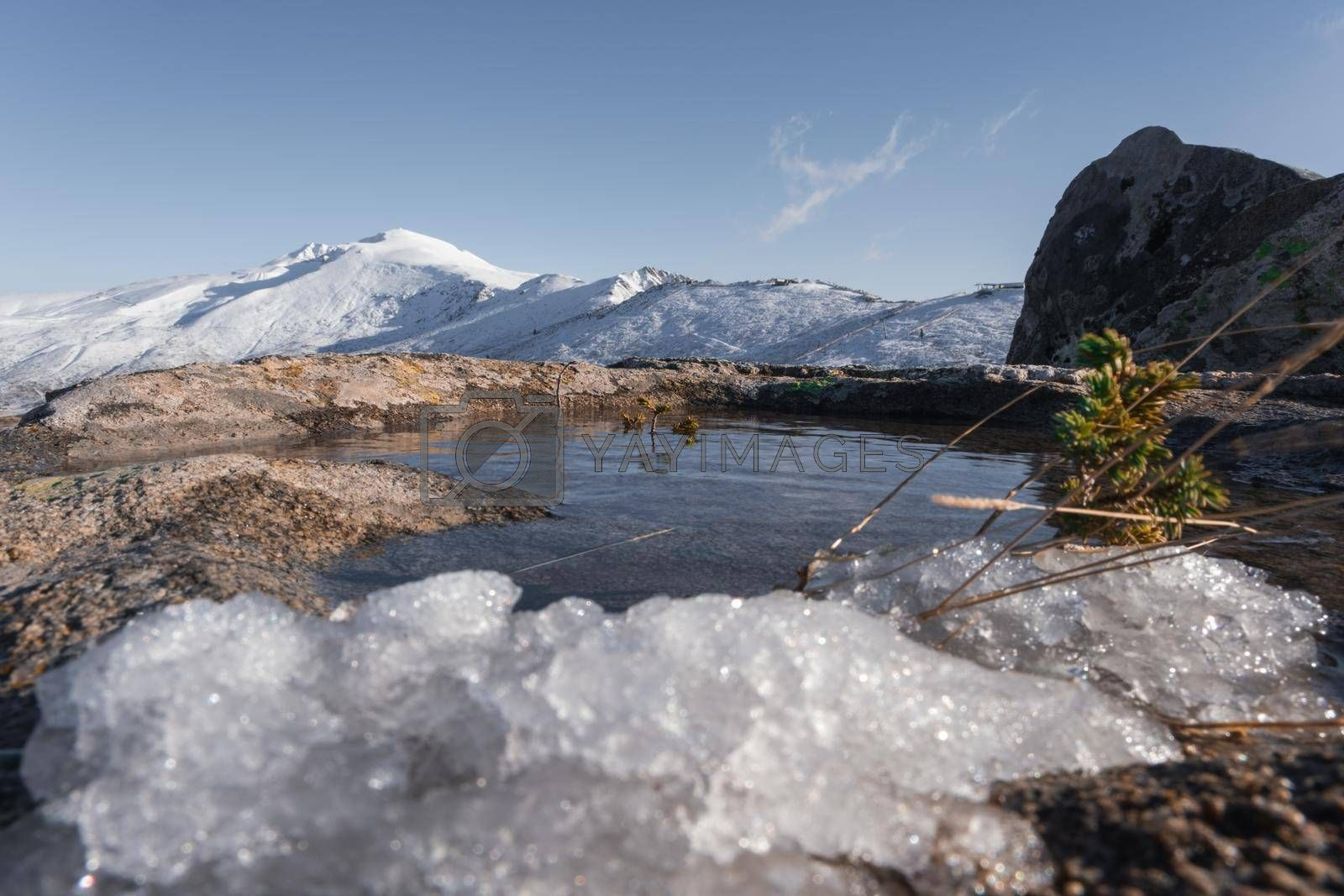 It depicts the puddle in the snowy mountain in Winter