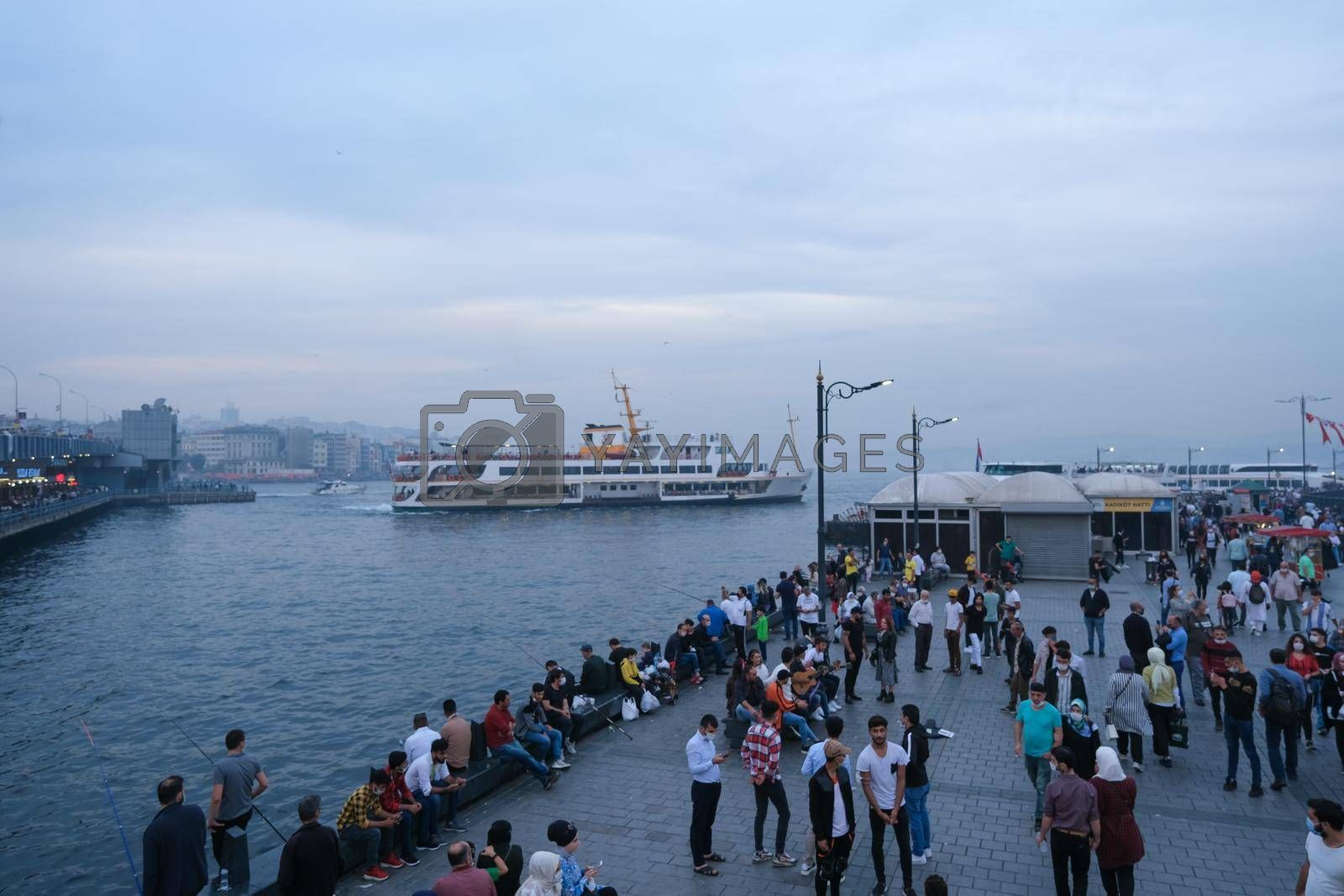 Eminonu, Istanbul, Turkey - November 05, 2020. The picture was taken in Autumn from the steps of Galata bridge in the afternoon and depicts the crowd in front of the coastal region along the ferry port
