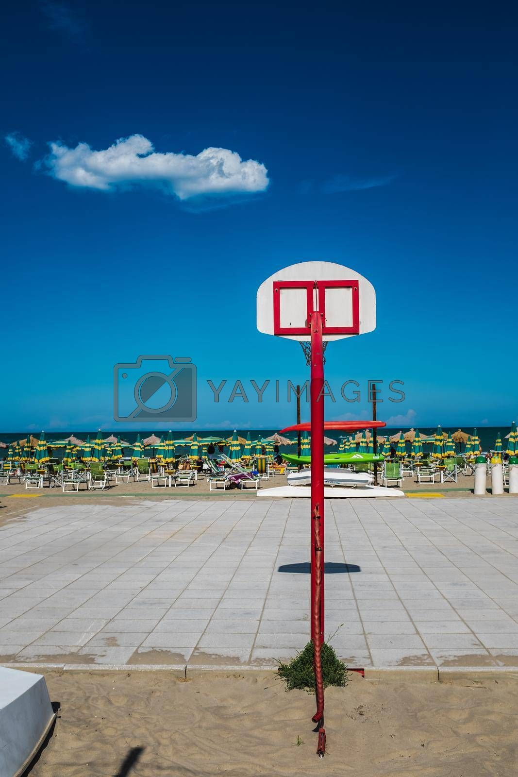 Pescara, Italy: rear view of a basketball hoop by beach. Bright colors in a summer day.