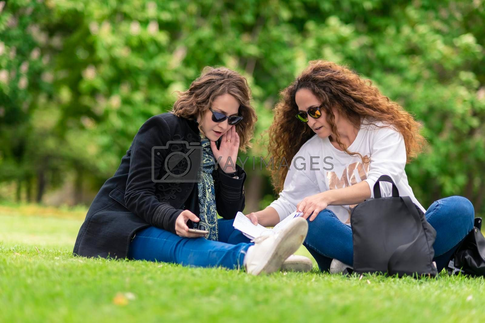 Talking and studying, with phone, relaxed in the park, sitting on the grass.