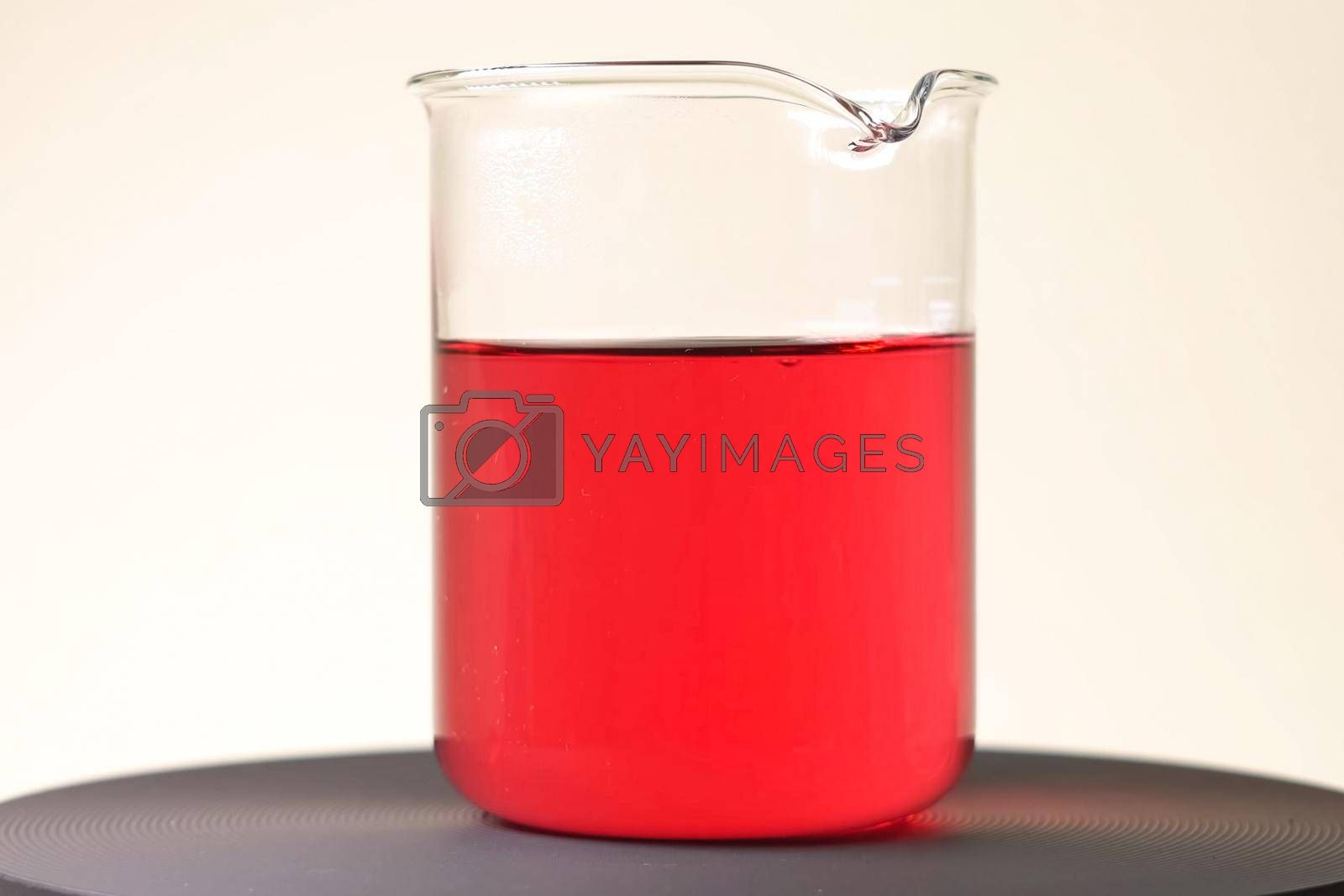 Red liquid in a glass glass. Chemical experiments