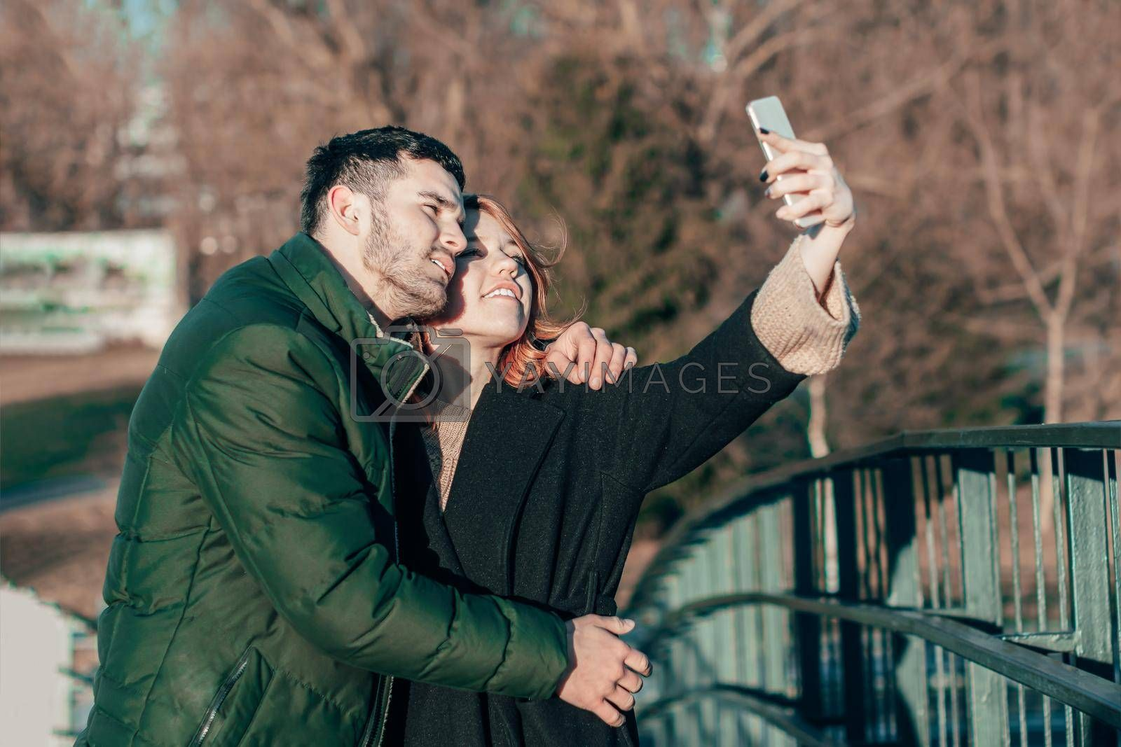 Cheerful Young Couple Making Selfie on the Bridge. Two Happy People Love Story on the Street