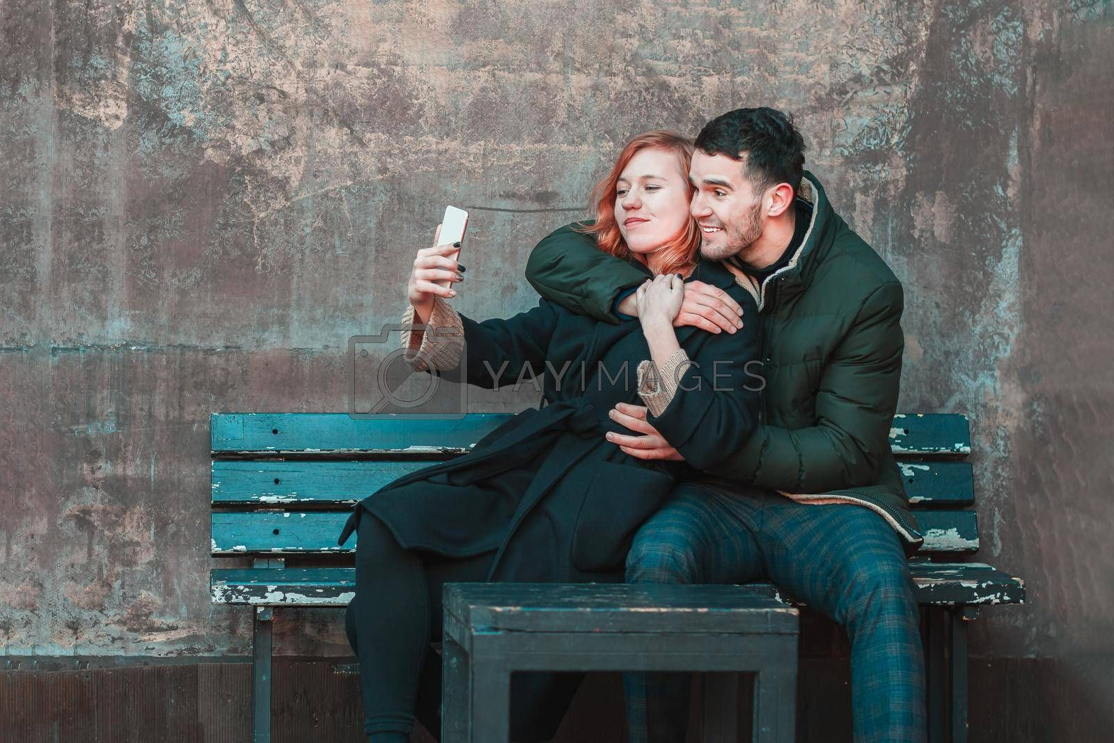 Cheerful Emotional Young Couple Sitting on the Bench and Making Selfie. Two Happy People Love Story on the Street