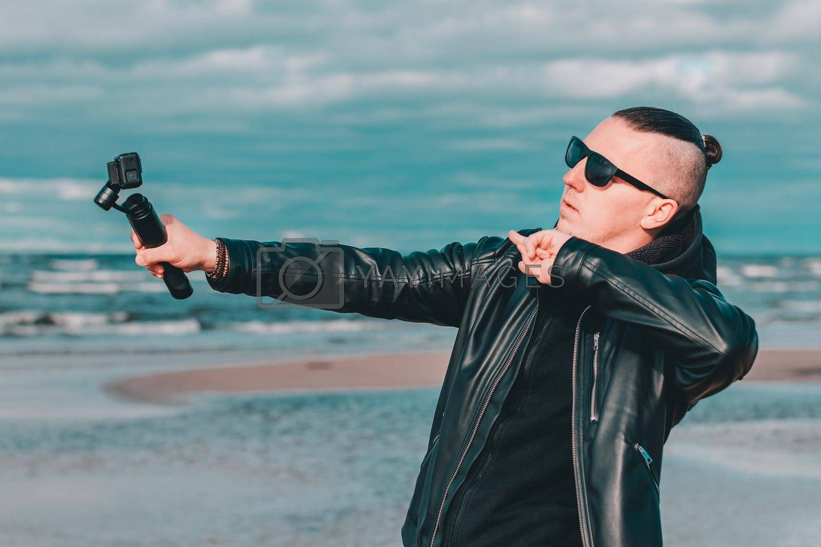 Young Blogger in Sunglasses Making Selfie or Streaming Video at the Beach Using Action Camera with Gimbal Camera Stabilizer. Hipster in Black Clothes Making Photo Against the Sea