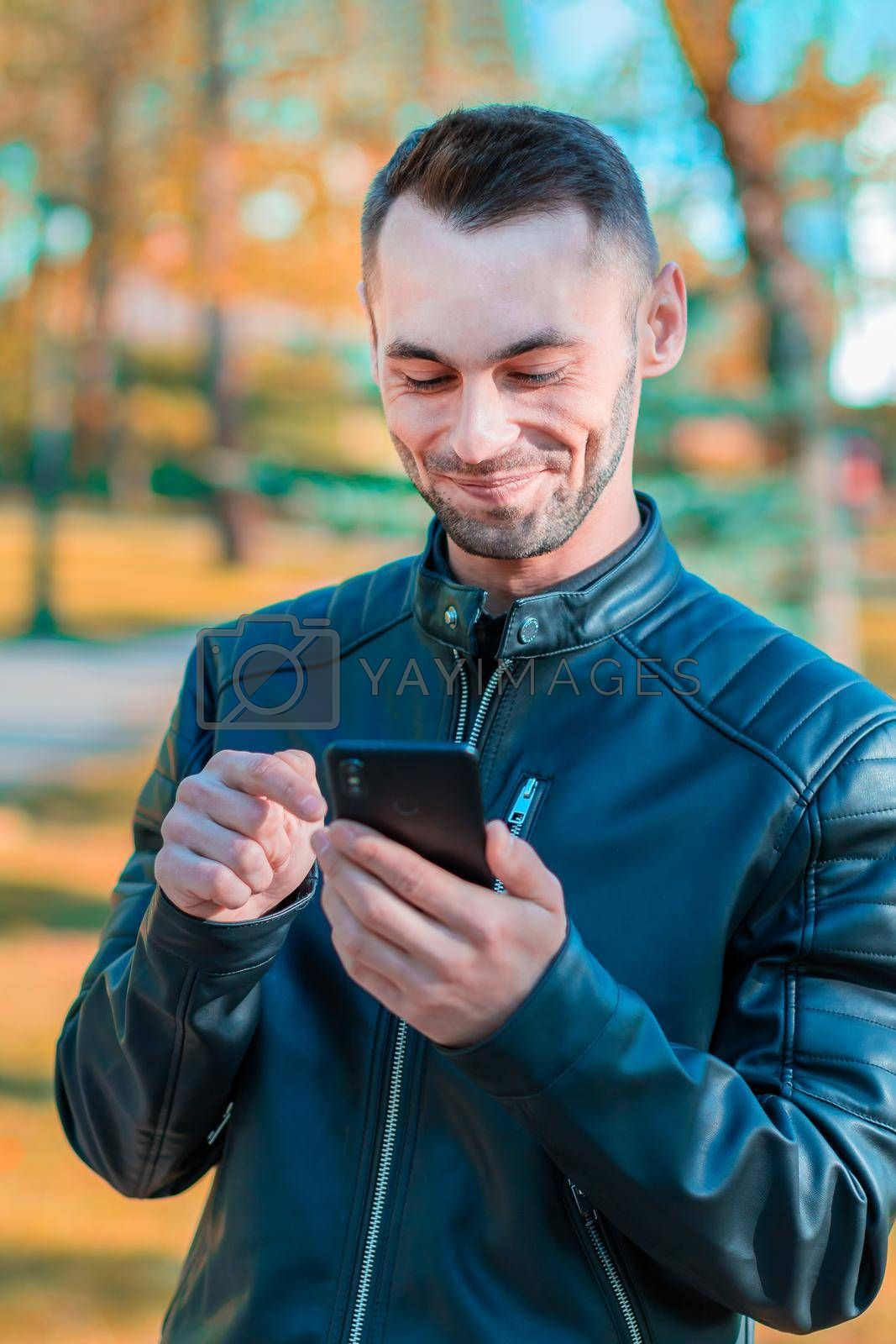 Youthful Satisfied Guy Using Black Smartphone at the Beautiful Autumn Park. Handsome Smiling Young Man with Mobile Phone at Sunny Day - Medium CloseUp Portrait
