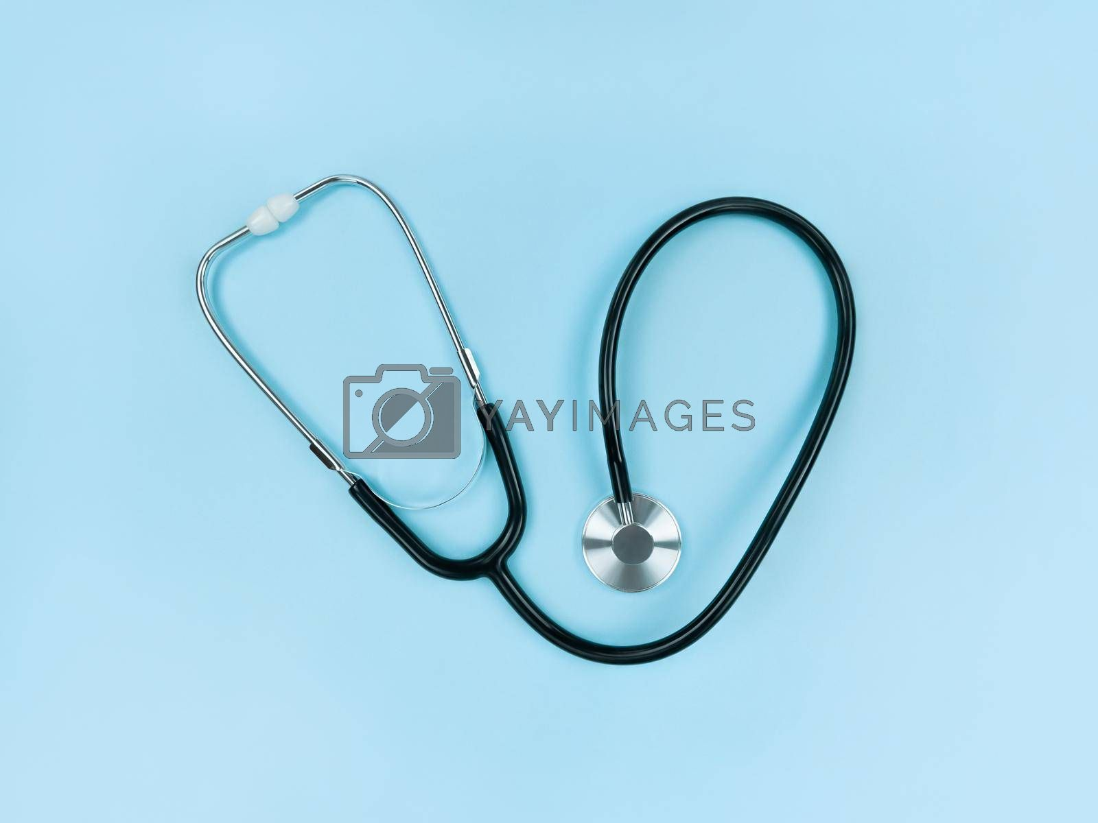 Black stethoscope on a soft blue background. Simple flat lay.