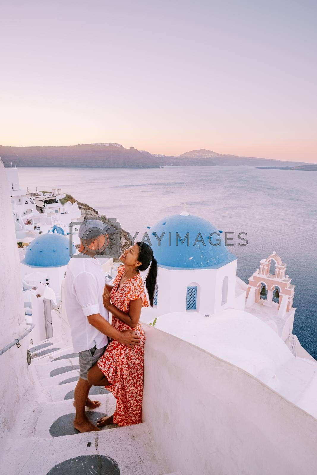 Santorini Greece, young couple on luxury vacation at the Island of Santorini watching sunrise by the blue dome church and whitewashed village of Oia Santorini Greece . Europe