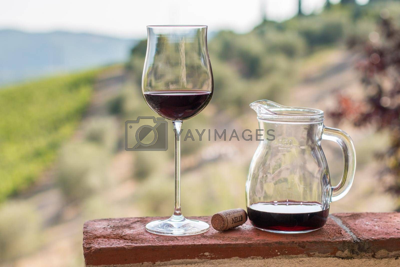 Enjoying a glass of red wine at Tuscany, Italy. Blurry wine yards in the background.