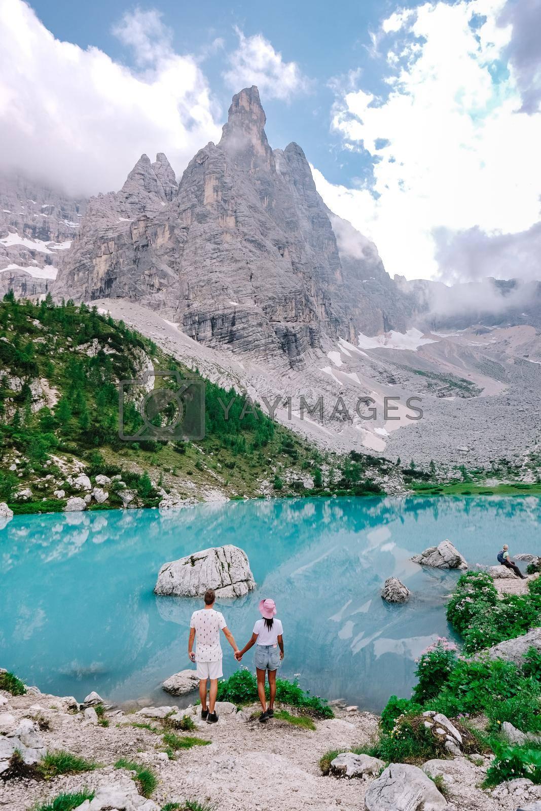 couple mid-age men and woman visiting the Italian Dolomites in Italy. Europe, Beautiful Lake Sorapis Lago di Sorapis in Dolomites