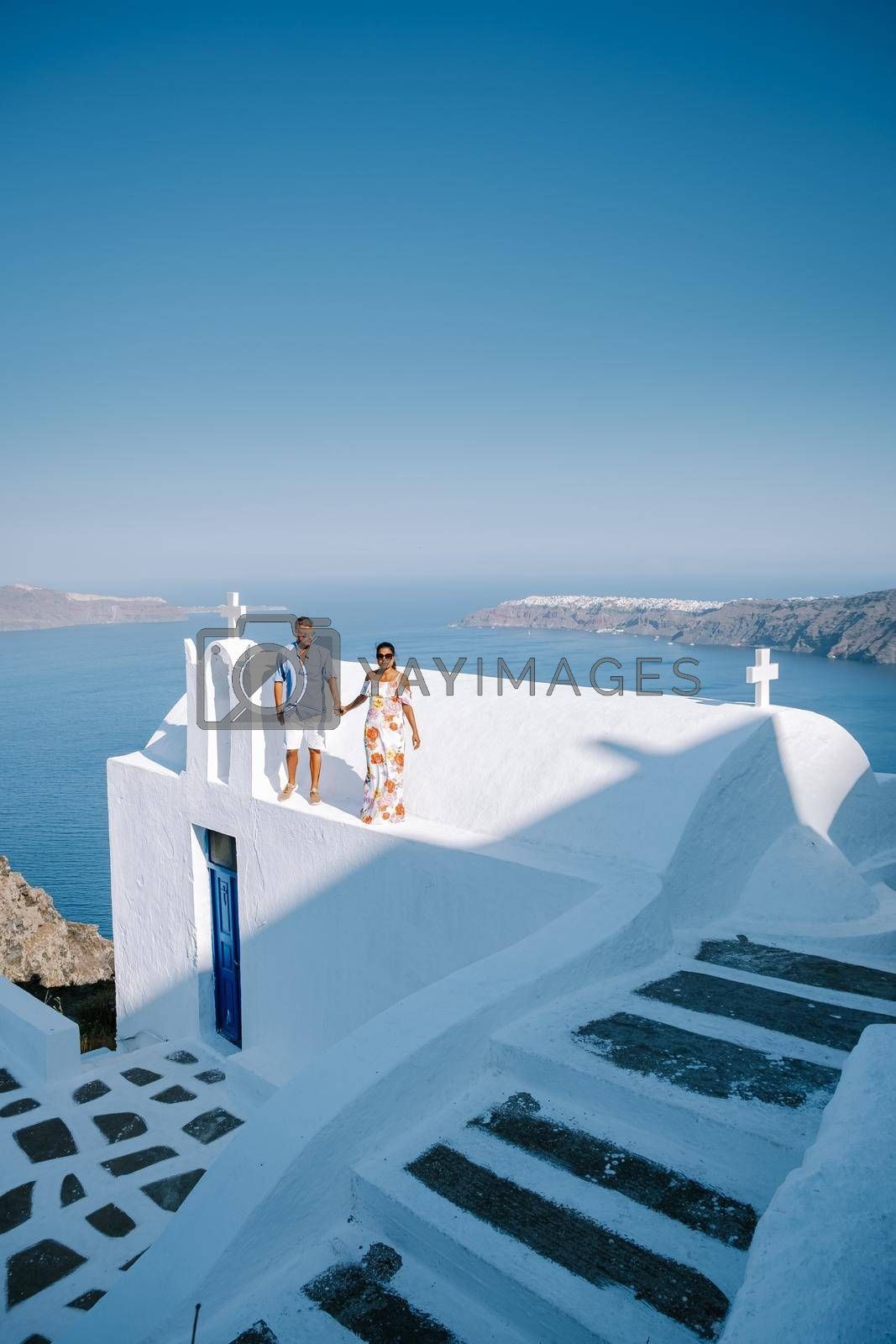couple visit Skaros rock Fira,Santorini Greece, young couple on luxury vacation at the Island of Santorini watching sunrise by the blue dome church and whitewashed village of Oia Santorini Greece . Europe