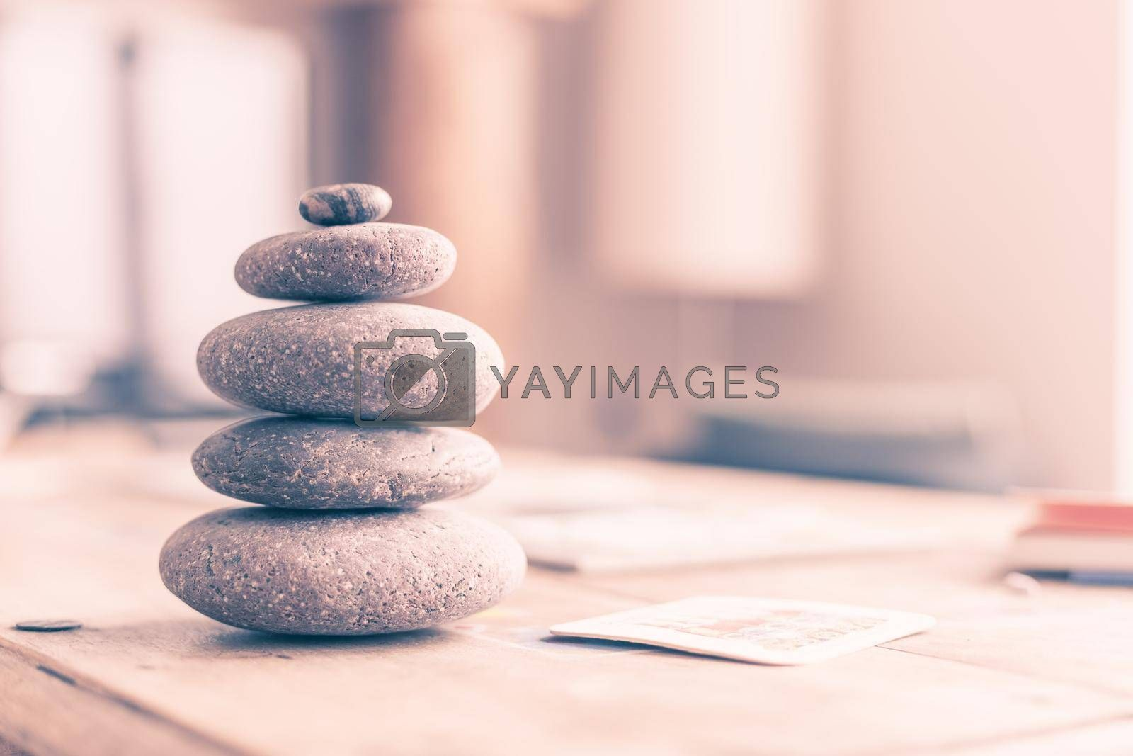 Feng Shui: Stone cairn in the foreground, blurry living room in the background. Balance and relaxation.